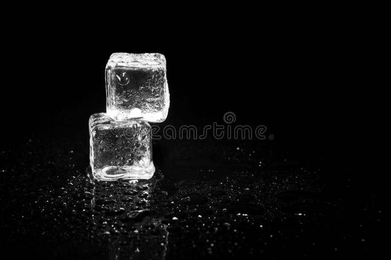 Ice cubes reflection on black table background. Abstract, bar, beautiful, block, blocks, bright, clean, clear, closeup, cold, cool, cracked, crushed, crystal stock photography
