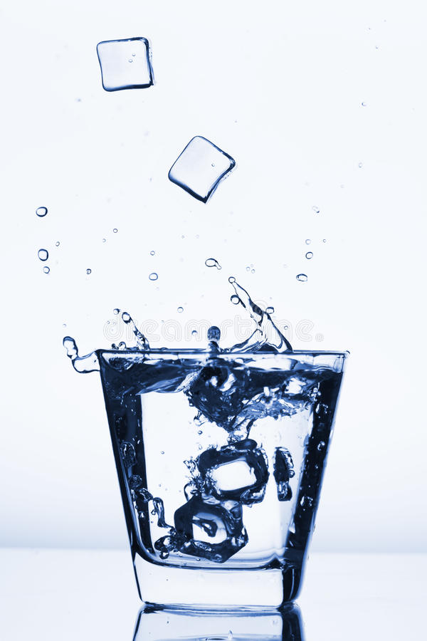 Ice cubes splashing into glass, ice cube dropped into glass of water, fresh, cold water, isolated on white blue, blue, caribian bl royalty free stock photos