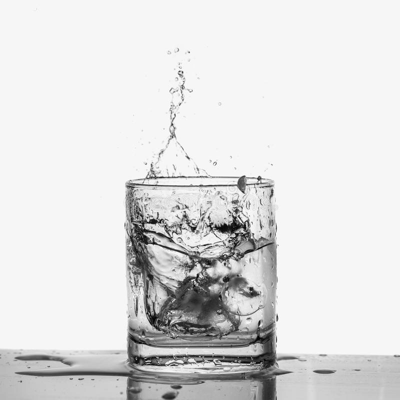 Ice cubes splashing into glass of water closeup, isolated on white royalty free stock images