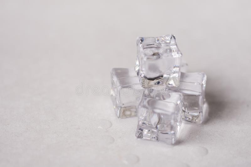 Ice cubes with water drops on the white marble background stock photo