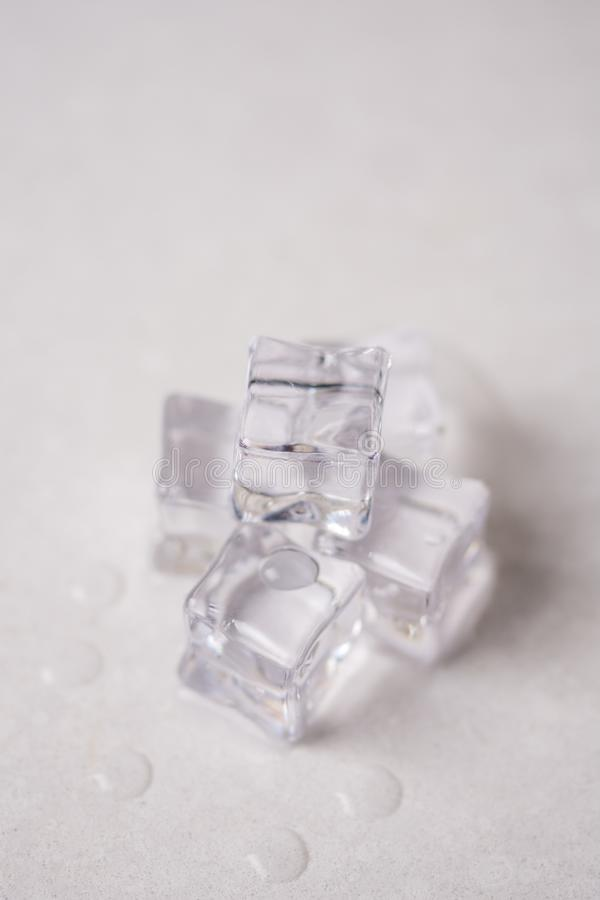 Ice cubes with water drops on the white marble background royalty free stock image