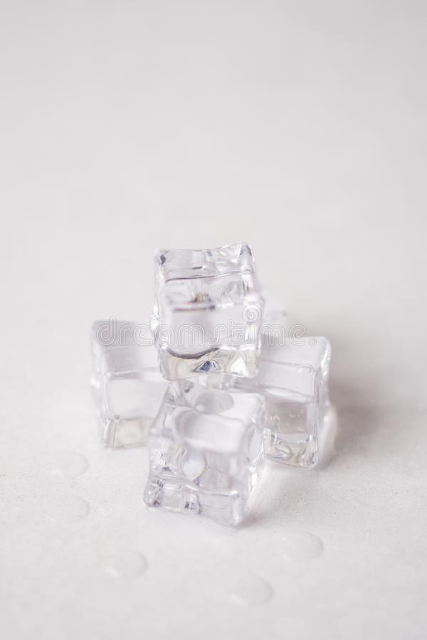Ice cubes with water drops on the white marble background royalty free stock photography