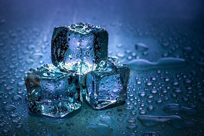 Ice cubes and water melt on cool background. Ice blocks with cold drinks or beverage. Cooling ice cube stock photos