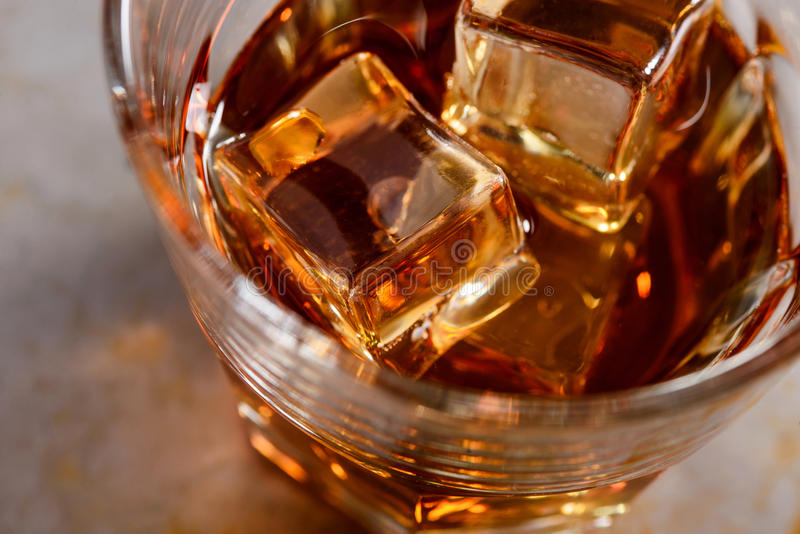 Ice cubes in whisky. Seductive ice cubes in whisky. The glass is full of alcohol. Ideal drink for clubs in a foreground royalty free stock photo