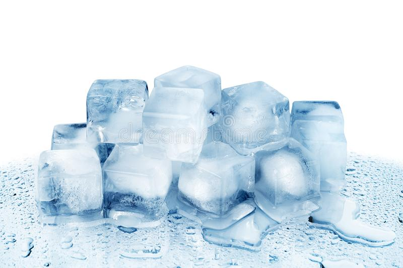 Ice cubes on white glass mirror background with reflection isolated close up, transparent frozen crushed blue ice cubes. Clear melted spilled cool water drops stock photo
