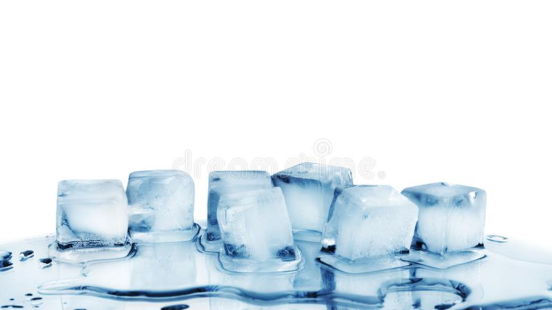 Ice cubes on white glass mirror background with reflection isolated close up, transparent frozen and melted crushed blue ice cubes stock photo