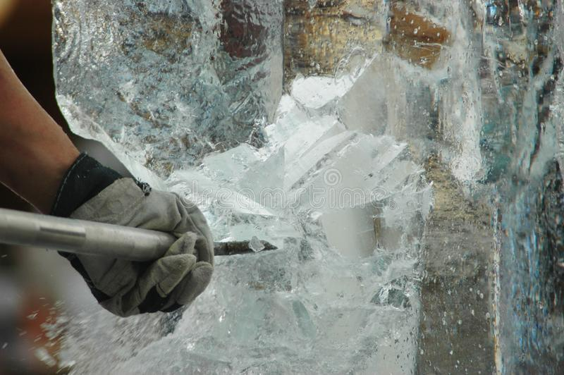 An ice-cutter carving an ice-statue. A man is carving a block of ice into a statue. Only his arm can be seen. He is using an ice-pick. Shards of ice are falling stock photos