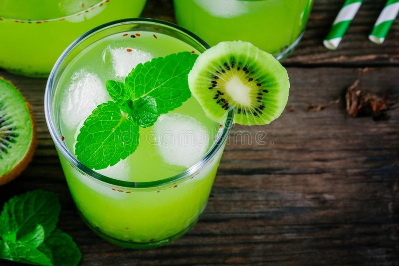 Ice drink with kiwi and mint in a glass on wooden background. Ice drink with kiwi and mint in a glass on a wooden background stock image