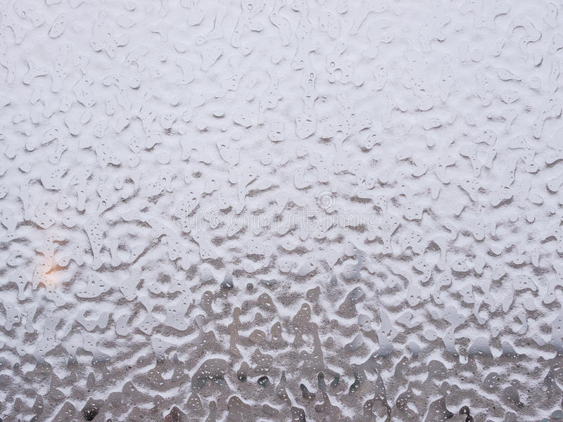Ice and drops on window. Texture of ice and drops on window glass in inclement winter weather. Close up. Icy rain background stock image