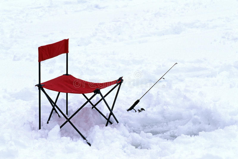 Ice fishing chair and pole. Empty red ice fishing chair and fishing pole in snow, Harriman Reservoir,Vermont stock photography