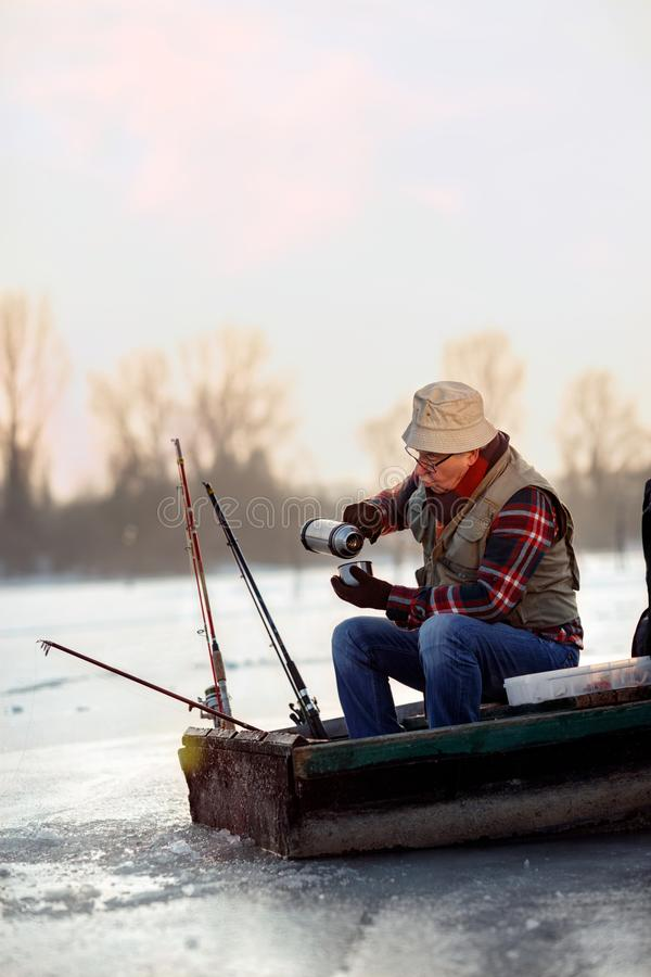 Ice fishing. elderly man sitting on frozen lake and drink tea stock images