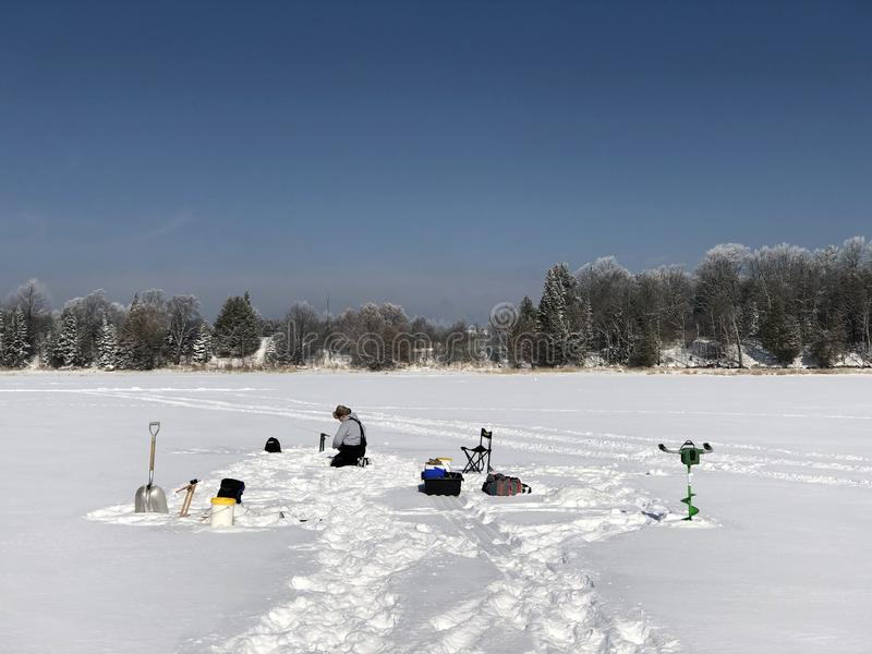 Ice fishing on a frosty morning. With snow covered trees in the background stock photo
