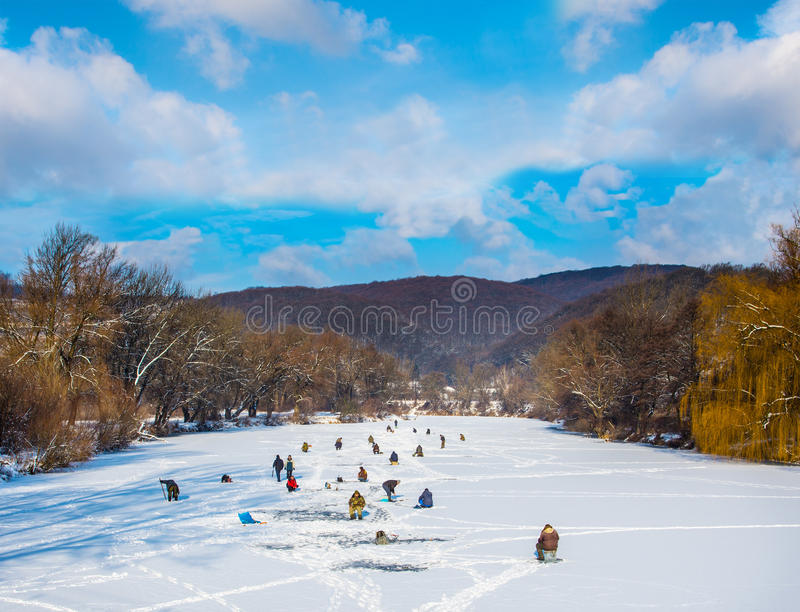 Ice fishing on a frozen river stock photo