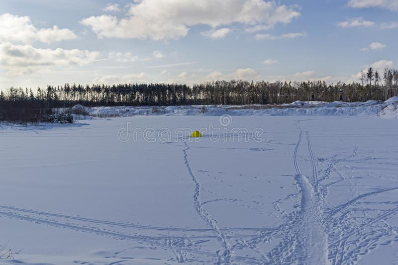 Ice fishing. Lonely fishing tent on a small forest lake stock photography