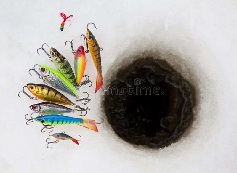 Ice fishing lures. Several ice fishing lures around ice hole royalty free stock photo