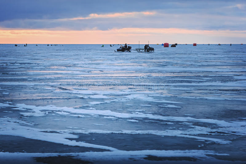 Ice fishing for smelts. Dawn on the frozen Baltic Sea Biosphere polygon. Ice fishing for smelts stock image