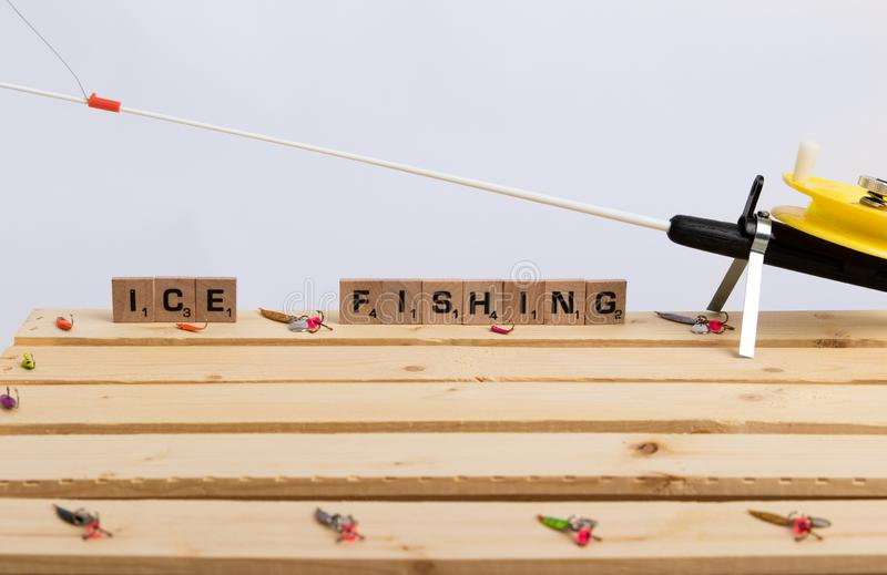 Ice Fishing Tackle and Pole. Ice fishing lures, tackle and pole on a wood background stock images