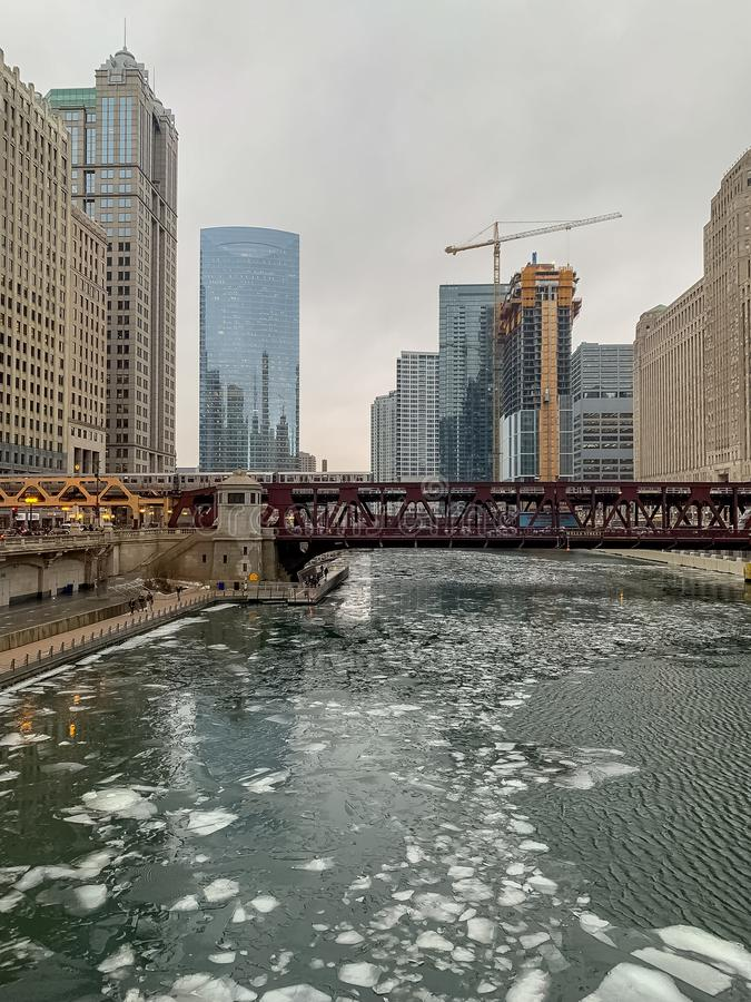 Ice floating on the Chicago River while el train crosses over on Wells Street royalty free stock photos