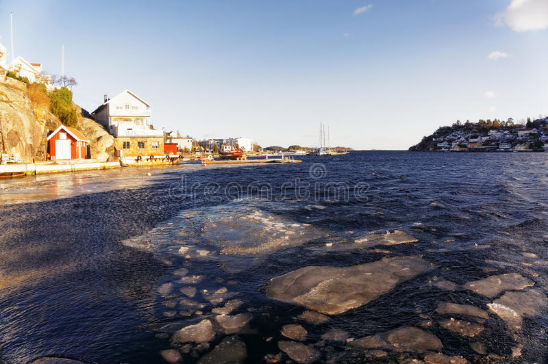 Ice floes on waves fjord. Blue water fjord surrounded by high cliffs of the island: Furuholmen. On the rocks colorful houses. Region of southeastern Norway stock photo