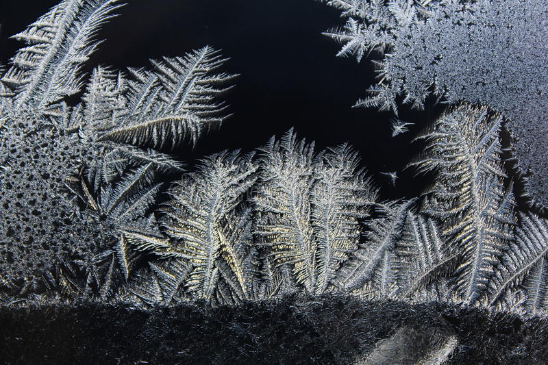 Ice flowers - frost pattern. Window frost (also called fern frost or ice flowers) forms when a glass pane is exposed to very cold air on the outside and royalty free stock image