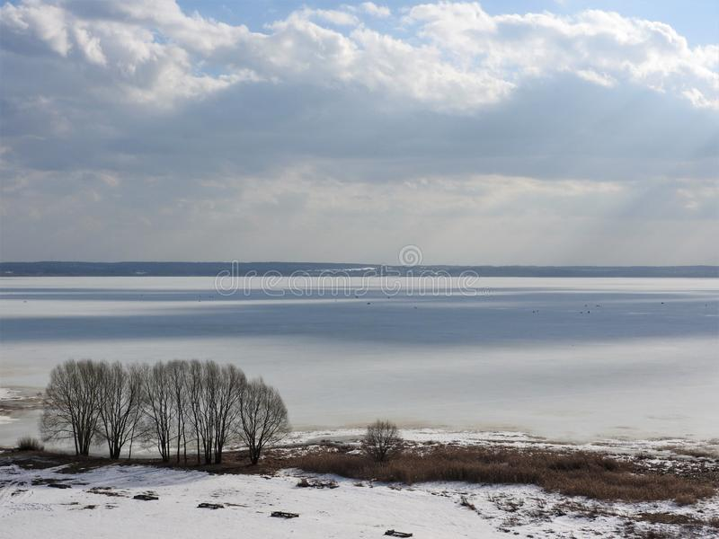 Ice frozen lake on a Sunny winter day in Russia. White snow and clouds in the blue sky. Beautiful winter landscape.  royalty free stock photos