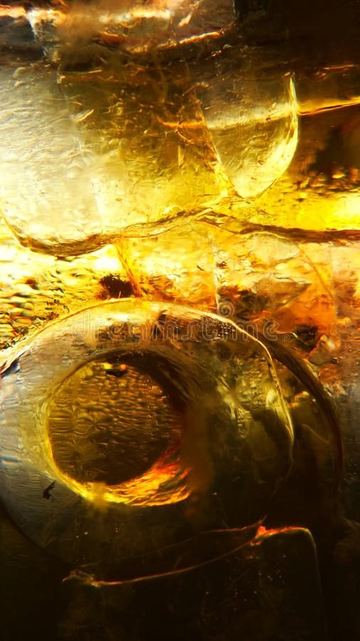 Ice in the glass and orange yellow beer droplets, abstract background royalty free stock images