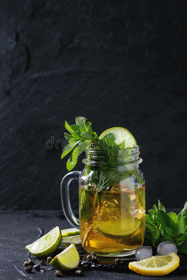 Ice green tea. Glass mason jar of Ice green tea with lime, lemon, mint and ice cubes on black slate stone board over black textured background. With copy space royalty free stock photography