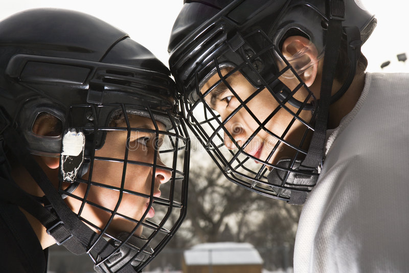 Ice hockey confrontation. Two ice hockey players in uniform facing off trying to intimidate eachother stock image