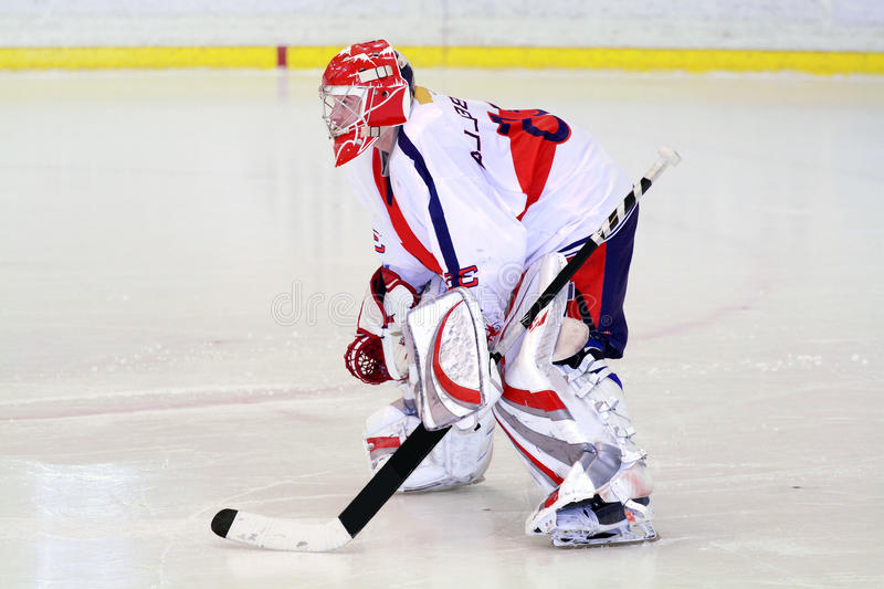 Ice hockey goalie. Hockey goalie in generic white and red equipmant on ice stock image