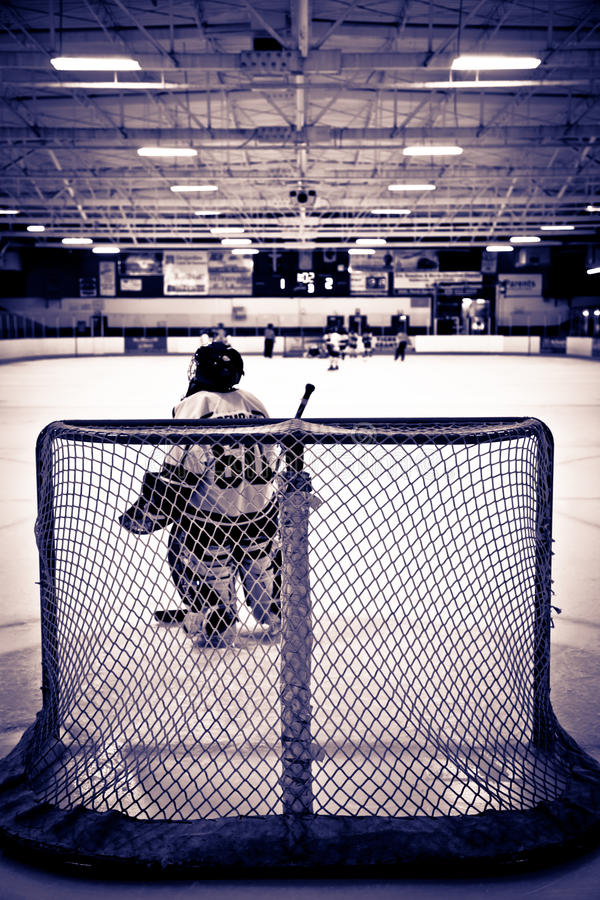 Ice Hockey Goalie. Young ice hockey goalie waiting in net royalty free stock photo