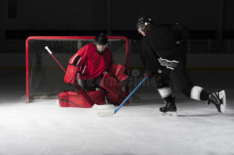 Ice hockey goalie with skaters shooting puck. Ice hockey goalie with skater. Picture taken on ice rink arena stock photography