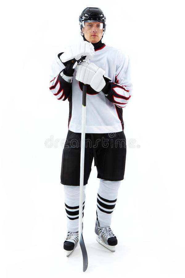 Ice-hockey player. Portrait of ice-hockey player with hockey stick royalty free stock photography