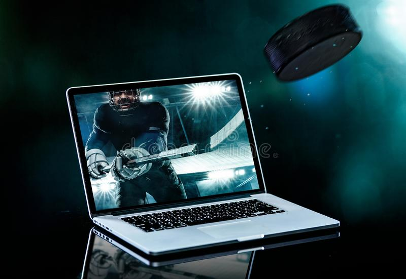 Ice Hockey player in the helmet and gloves on stadium with stick. Laptop on the table with design for bookmaker. Hockey player in the mask on stadium stock image