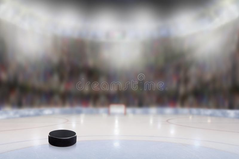 Ice Hockey Puck in Rink Arena With Copy Space. Low angle view of ice hockey puck on ice with deliberate shallow depth of field on brightly lit stadium background royalty free stock images