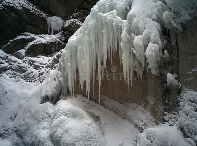 Ice icicles on the rocky mountain with a snow stock photography