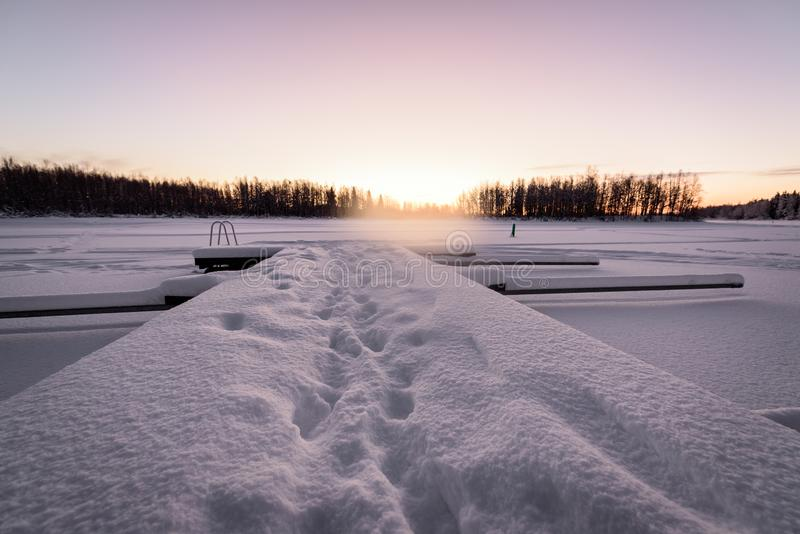 The ice lake and forest has covered with heavy snow and nice blue sky in winter season at Holiday Village Kuukiuru, Finland. Background beautiful blizzard stock image