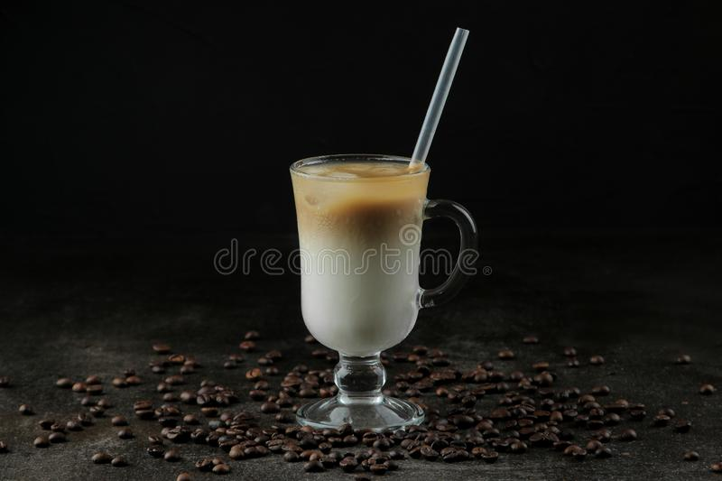 Ice latte or Iced coffee with milk and ice cubes in a glass beaker against a dark background. refreshing drink. summer drink. Ice latte or Iced coffee with milk stock images