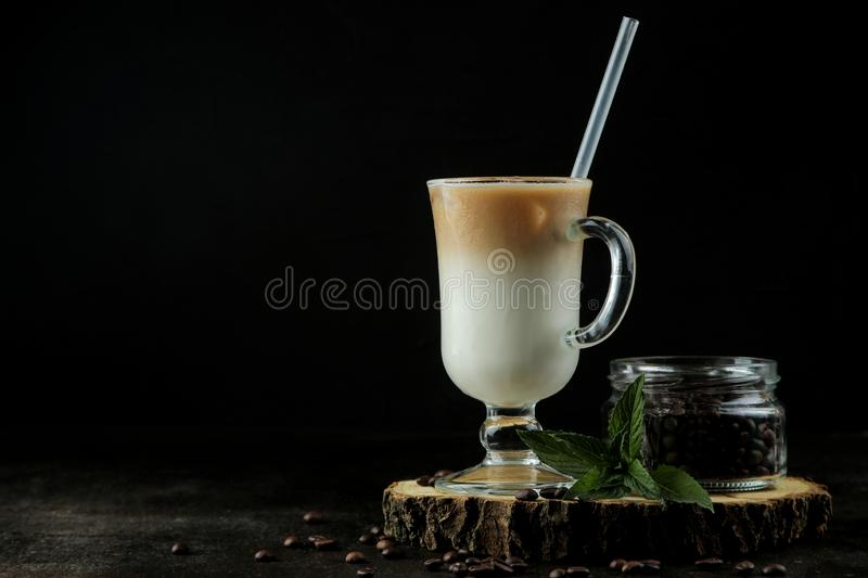 Ice latte or Iced coffee with milk and ice cubes in a glass beaker against a dark background. refreshing drink. summer drink stock photos