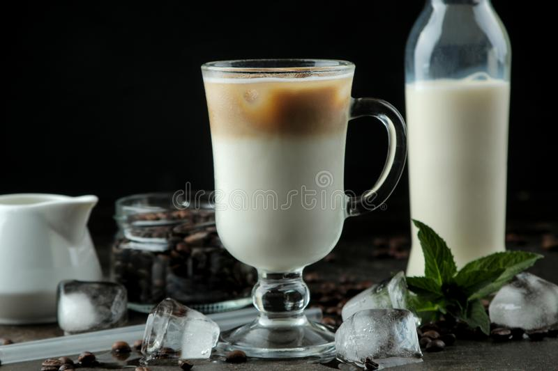 Ice latte or Iced coffee with milk and ice cubes in a glass beaker against a dark background. refreshing drink. summer drink. Ice latte or Iced coffee with milk stock image