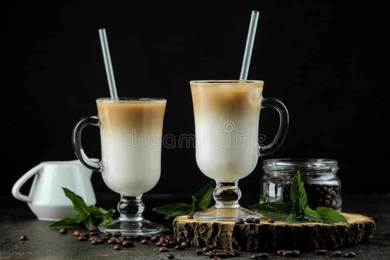 Ice latte or Iced coffee with milk and ice cubes in a glass beaker against a dark background. refreshing drink. summer drink. Ice latte or Iced coffee with milk royalty free stock photography