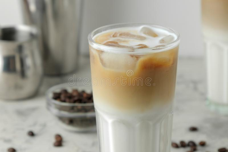 Ice latte or Iced coffee with milk and ice cubes in a glass beaker on a light background. refreshing drink. summer drink. Ice latte or Iced coffee with milk and royalty free stock image