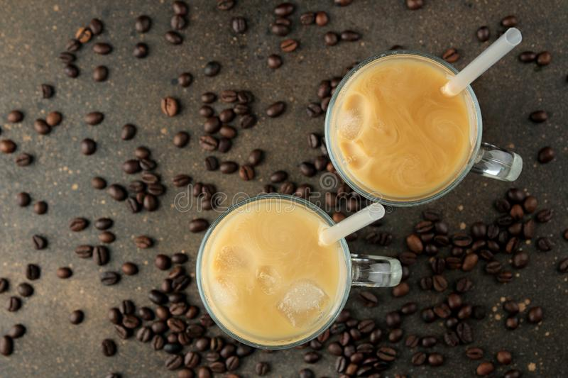 Ice latte or Iced coffee with milk and ice cubes in a glass beaker against a dark background. refreshing drink. summer drink. top. View royalty free stock image
