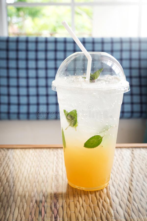 Ice lemon tea with mint and soda. In plastic cup. Refreshment drink. With cafe view and dark vignette stock image