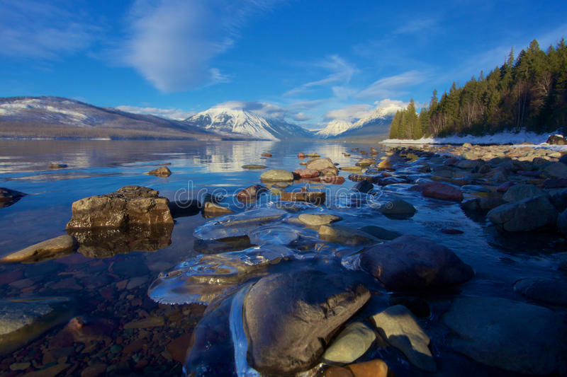 Ice-Locked Rocks on the Warming Wintery Shores of Lake McDonald at Glacier National Park, Montana, USA royalty free stock photography