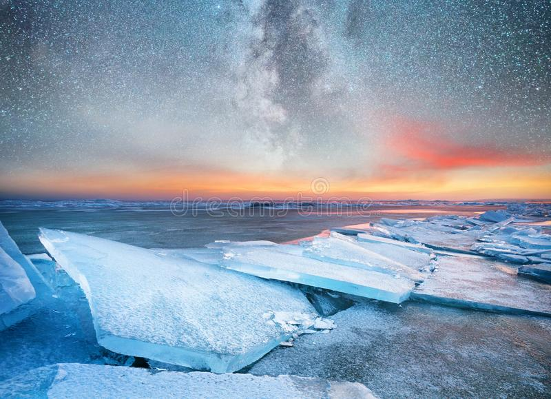 Ice on the ocean shore at the night time. Sea bay and stars at the night time. Milky way above ocean, Norway. royalty free stock images