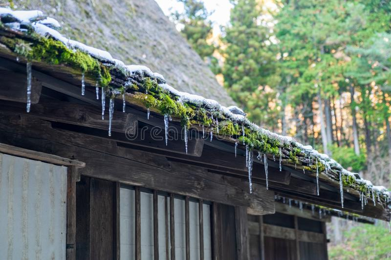 Ice perched on the roof after snow begins to melt. Ice perched on the roof after the snow begins to melt stock photos