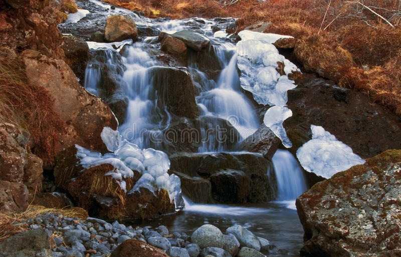 Ice sculpted by small waterfall royalty free stock images