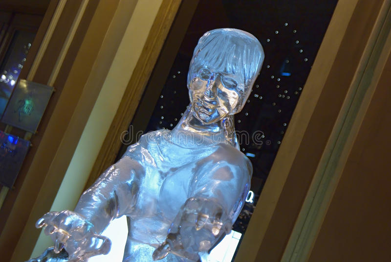 Ice sculpture of a girl against shopwindow in outdoors stock photo