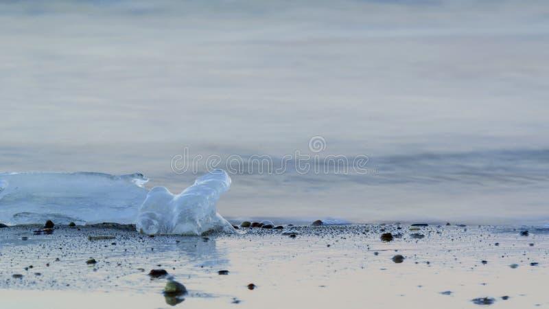 ICE ON THE SEA SHORE. Lump of ice on the sea shore stock photo