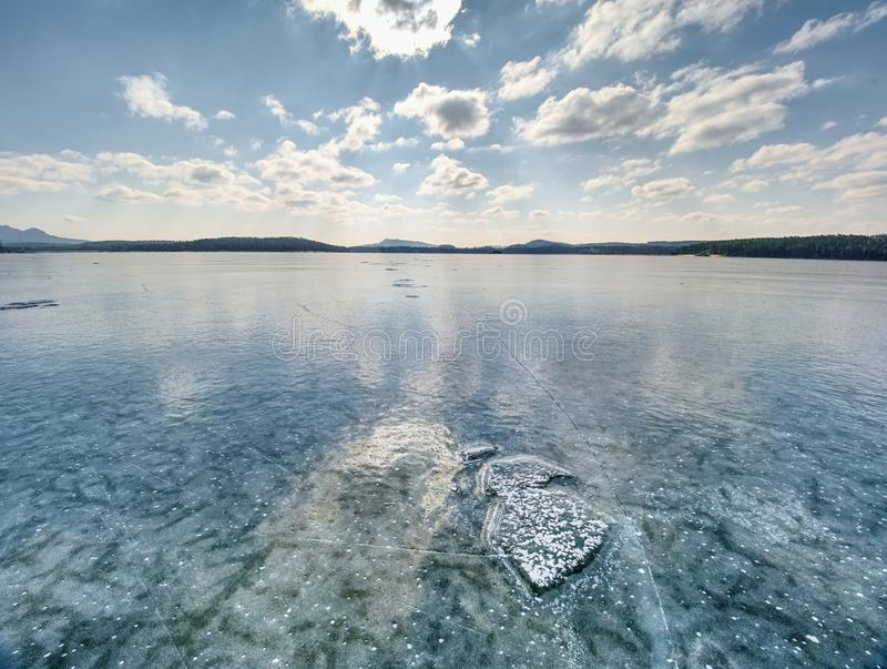 Ice shards on a frozen lake. The rays of the sun creat rainbow shadows. In the cracks of the ice royalty free stock photo